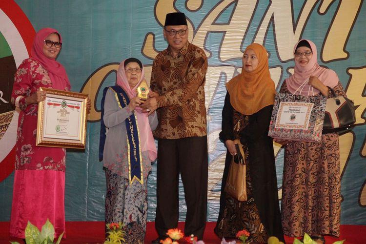 Rais Syuriah PBNU KH Asad Ali menyerahkan penghargaan ke Nyai Hj Muchasonah (nomor dua dri kiri), perwakilan keluarga besar KH Bisri Syansyuri yang dianugerahi gelar Pahlawan Santri dalam ajang Santri of The Year 2017 di Jakarta, Minggu (22/10/2017).