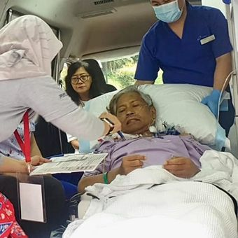 Petugas PPLN Singapura memberikan penjelasan tata cara mencoblos kepada Bigman Sirait yang mencoblos di dalam ambulans di kompleks KBRI di Singapura, Minggu (14/4/2019). (KOMPAS.com/ERICSSEN)