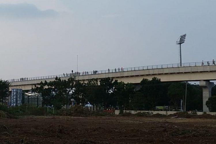 Para penumpang LRT Palembang berjalan diatas rel menuju ke stasiun Jakabaring, karena kereta mendadak mogok, Minggu (12/8/2018)