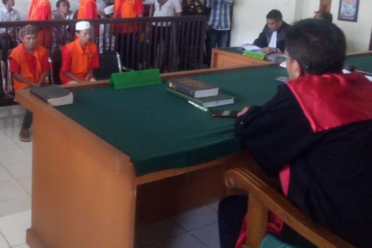 Acundra (21) dan Ridwan (45) dua terdakwa kasus pembunuhan Sofyan (44) sopir taksi online yang tewas dibunuh serta dirampok, ketika mengahadapi persidangan di Pengadilan Negeri Klas 1 Palembang, Sumatera Selatan, Selasa (2/4/2019).