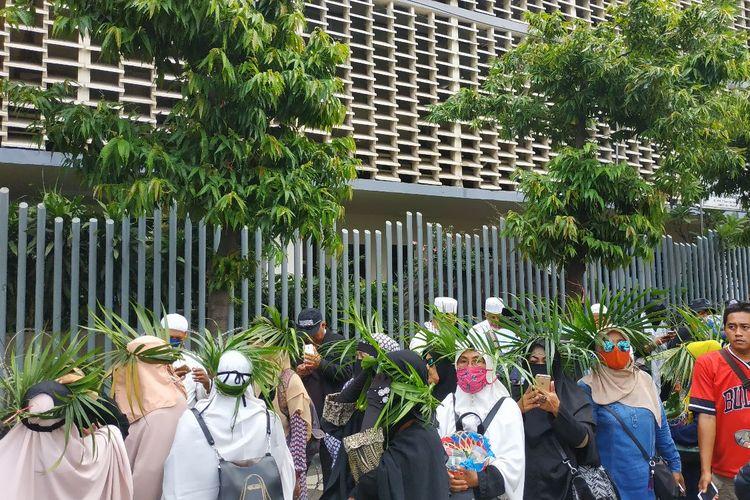 Sejumlah perempuan paruh baya mengenakan ikat kepala dari daun palem sebagai simbol aksi damai di Bawaslu pada Jumat (10/5/2019) siang.