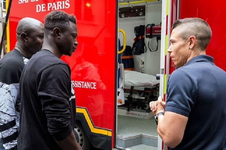 Mamoudou Gassama (tengah) ketika mengunjungi markas pemadam kebakaran di Paris, Perancis, Selasa (29/5/2018). Gassama menuai pujian setelah memanjat gedung demi menyelamatkan bocah empat tahun.
