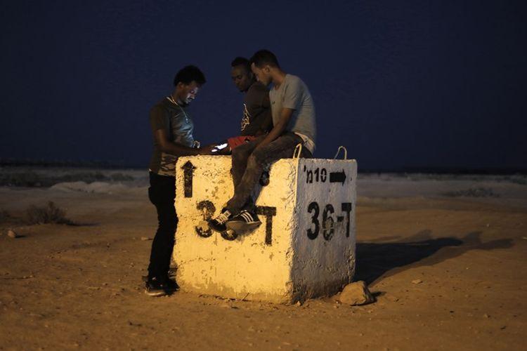 Para migran Afrika menghabiskan waktu di luar pusat penampungan Holot di gurun pasir Negev, selatan Israel.