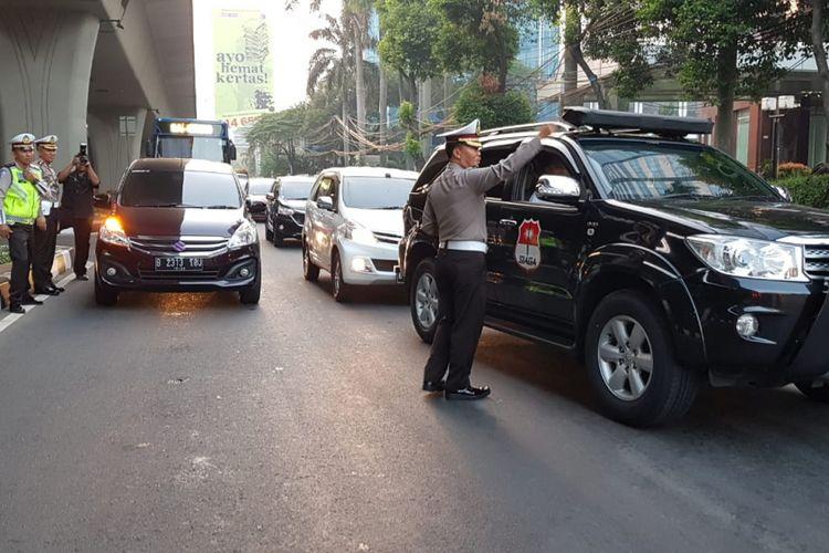 Mobil yang melanggar peraturan pembatasan kendaraan berdasarkan nomor pelat ganji dan genap mulai dialihkan di Simpang Pancoran, Jakarta Selatan, Rabu (18/7/2018).
