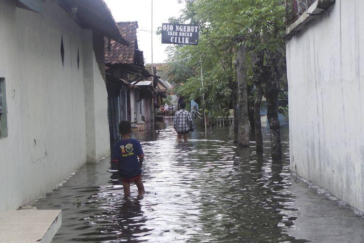 Sejumlah warga Kelurahan Tirto, Kecamatan Pekalongan Barat, Kota Pekalongan, Jawa Tengah, berjalan menerjang banjir di wilayah tersebut, Selasa (16/1). Selain di Tirto, dampak banjir juga antara lain dirasakan warga Kelurahan Pasirkratonkramat, Pekalongan Barat. Hujan deras disertai petir  pada Minggu dan Senin (14-15/1/2018) malam menyebabkan Kali Bremi meluap.  Kompas/Aditya Putra Perdana (DIT) 16-01-2018