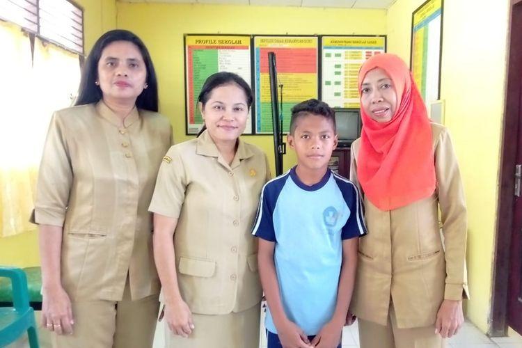 Sandi Lawerang siswa kelas VI SD Inpres 58 Ambon berfose bersama guru-gurunya di ruang guru sekolah tersbeut, usai diwawancarai Kompas.com, Senin (19/8/2019)
