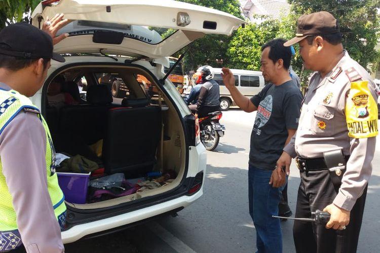 Petugas kepolisian di Lamongan saat memeriksa isi salah satu mobil, dalam razia menghadang massa berangkat hadiri people power di Jakarta.