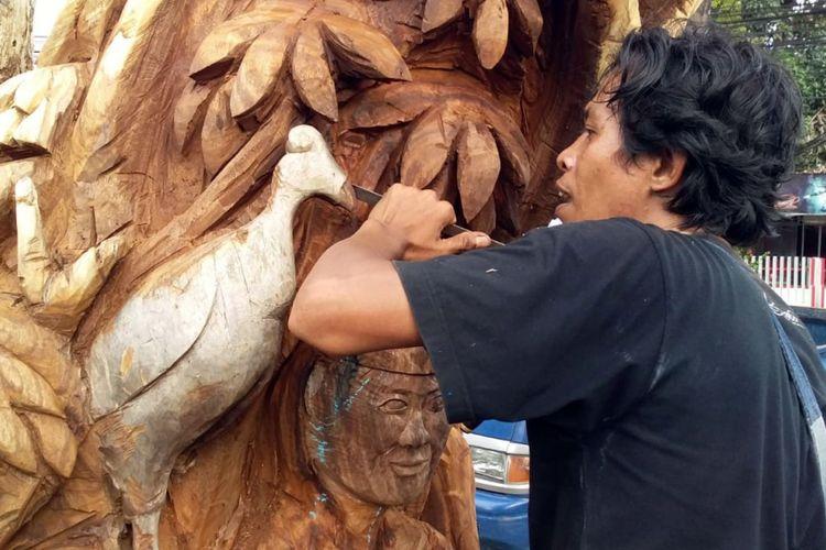Seniman pahat Gorontalo, Pipin Idris sedang membentuk burung Maleo (Macrocephalon maleo) pada sebuah pohon mati di RTH taman Kota.