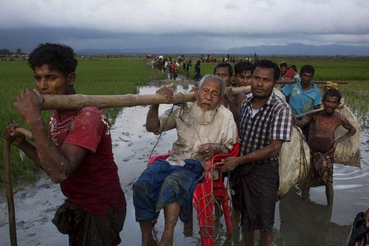 Pengungsi Rohingya dari Rakhine, Myanmar, memikul seorang kakek renta ketika melintasi perbatasan menuju Banglades.