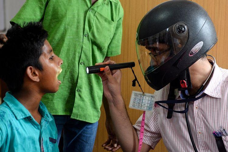 Dokter di India memeriksa pasien sambil mengenakan helm, sebagai bentuk kritik dan protes akan kurangnya keamanan tenaga medis yang kerap mendapat kekerasan dari pasien dan keluarga pasien.