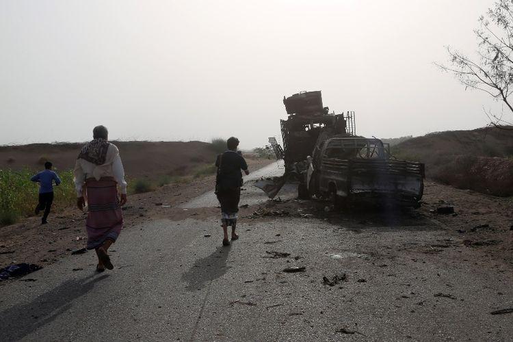 Warga Yemen melintas di dekat bangkai kendaraan yang hancur akibat pertempuran antara pasukan pemerintah dengan pemberontak Houthi di dekat Hodeidah.