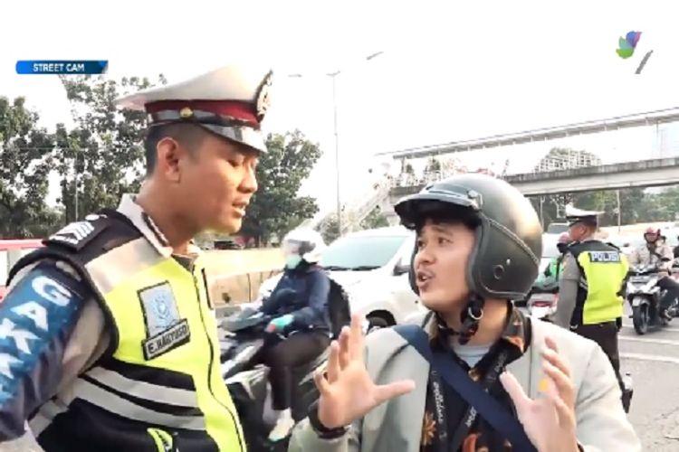 Polisi berdebat dengan pengendara motor.