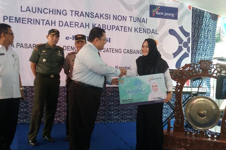 Bupati Kendal Mirna Anissa, secara simbolis menerima kartu e-retribusi dari kepala bank Jateng cabang Kendal. Kompas.Com/Slamet Priyatin