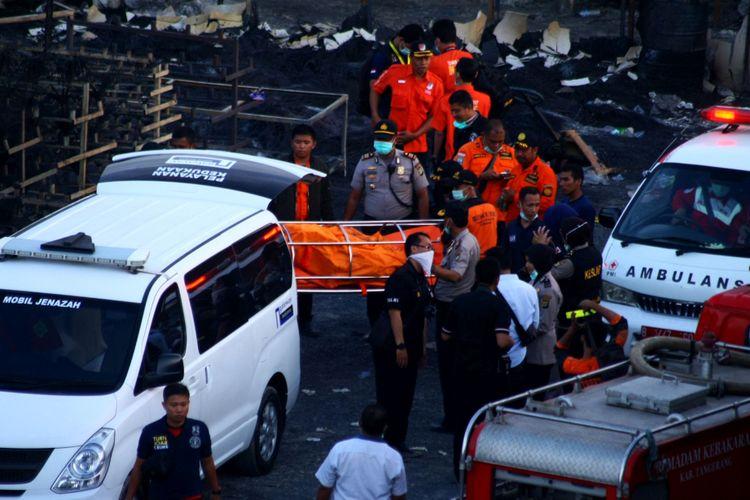 Petugas PMI dan Basarnas mengevakuasi jenazah korban kebakaran pabrik kembang api di Kosambi, Tangerang, Banten, Kamis (26/10/2017). Kebakaran yang diduga akibat dari ledakan salah satu tempat pembuatan kembang api yang baru beroperasi dua bulan ini menewaskan setidaknya 47 orang karyawan dan puluhan lainnya terluka bakar.