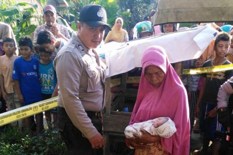Warga memperlihatkan temuan bayi perempuan di Desa Blang Weu Baroh, Kecamatan Blang Mangat, Kota Lhokseumawe, Minggu (14/10/2017)