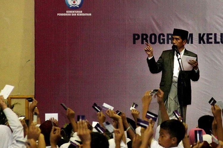 Presiden Joko Widodo (kiri) disaksikan Kepala Staf Kepresidenan Moeldoko (kanan) membagikan Kartu Indonesia Pintar (KIP) saat acara penyaluran Bantuan Non Tunai dan Program Keluarga Harapan di Serang, Banten, Rabu (14/3). Menurut data Kemensos penyaluran bantuan Program Indonesia Pintar untuk siswa dari keluarga tidak mampu telah dibagikan kepada 593 ribu siswa dengan jumlah bantuan mencapai Rp303,75 miliar.