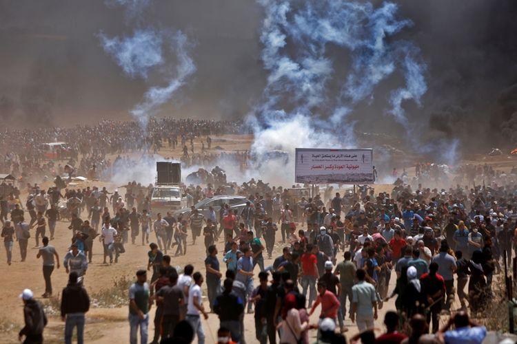Ribuan warga Palestina melarikan diri dari serangan gas air mata yang dilepaskan pasukan Israel di dekat perbatasan di Jalur Gaza pada Senin (14/5/2018). Bentrok terjadi jelang peresmian kedutaan AS di Yerusalem.