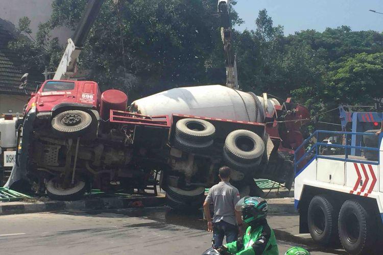 Sebuah truk molen terguling di ruas Jalan Jatibaru, Jakarta Pusat, Jumat (13/4/2018). Tiga mobil derek dari Dinas Perhubungan DKI Jakarta pun dikerahkan untuk memindahkan truk tersebut.