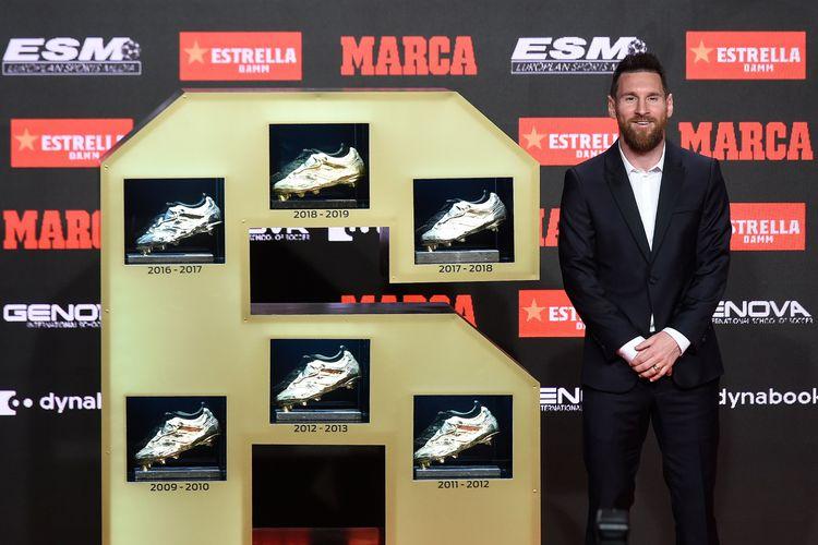 Pemain Barcelona, Lionel Messi, berpose di samping enam sepatu emas yang dia kumpulkan sepanjang karier. Gambar diambil pada Rabu (16/10/2019) waktu setempat, seusai dia menerima sepatu emas keenam di Antigua Fabrica Estrella Damm, Barcelona, Spanyol.