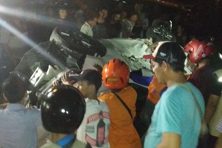 Petugas kepolisian dibantu warga mencoba mengevakuasi mobil Toyota Yaris yang tertabrak kereta api di perlintasan kereta api Purwosari, Solo, Jawa Tengah, Senin (20/5/2019) malam.