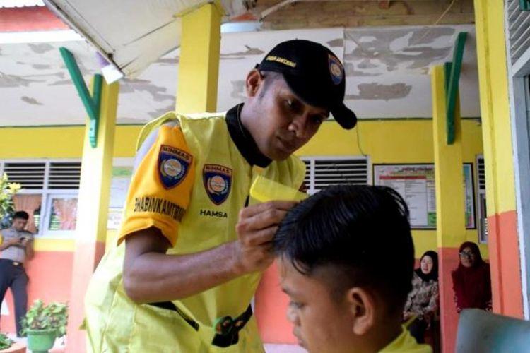 Anggota Bhabinkamtibmas Polsek Pasarwajo yang melakukan cukur gratis buat anak sekolah dan masyarakat. Melalui cukur gratis, ia menyampaikan pesan-pesan Bhabinkamtibmas kepada masyarakat