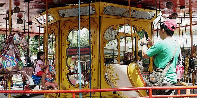 Dimas Prasetyo, warga Solo, menemani putrinya, Kanya, yang sedang menaiki komidi putar di Taman Hiburan Rakyat Sriwedari, Solo, Jawa Tengah, Minggu (15/10/2017). Setelah beroperasi selama 32 tahun, tempat hiburan yang memiliki aneka wahana permainan dan menyajikan pertunjukan musik ini akan ditutup awal Desember mendatang.