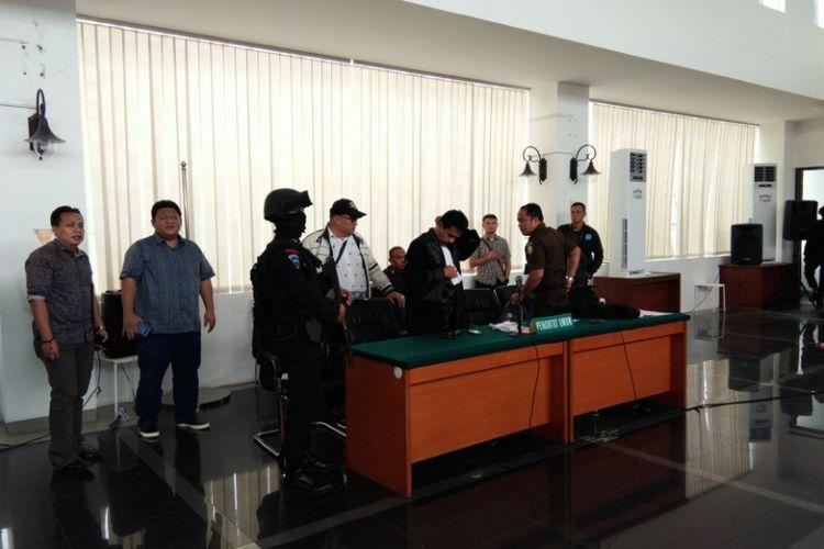 Anggota Brimob dan beberapa polisi berpakaian preman saat memberikan pengawalan terhadap tim Jaksa Penuntut Umum (JPU) dalam sidang vonis Buni Yani, di Gedung Dinas Perpustakaan dan Arsip (Dispusip), Jalan Seram, Kota Bandung, Selasa (14/11/2017).
