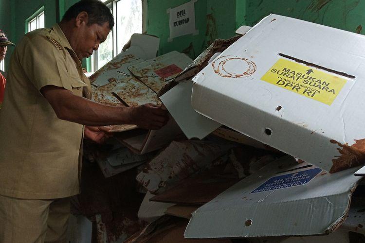 Sejumlah petugas sedang mengevakuasi kotak suara yang rusak akibat hujan deras di Desa Cibentang, Kecamatan Ciseeng Kabupaten Bogor, Senin (15/4/2019)