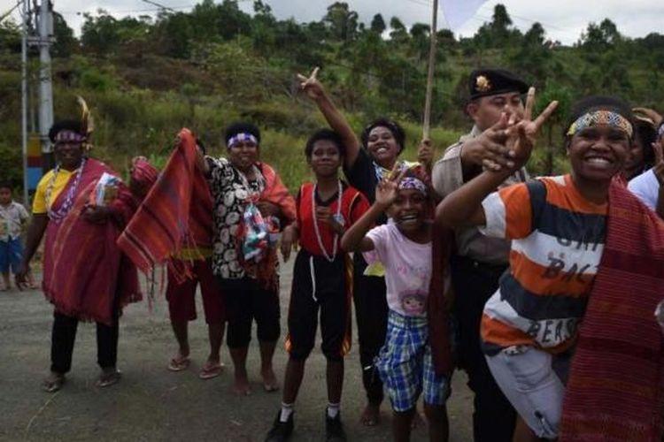 Warga Papua mengibarkan Bendera Merah Putih saat menyambut kedatangan Presiden Joko Widodo dan rombongan di Jayapura, Papua, 9 Mei 2015.