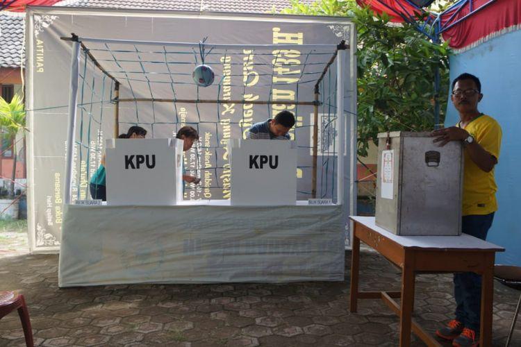 Ilustrasi bilik suara: Dengan berpakaian lengkap sepatu sepak bola dan kostum timnas berbagai negara yang ikut serta dalam Piala Dunia 2018, para petugas KPPS di TPS 14 Kelurahan Karawang Kulon seolah menjadi pemain yang menggiring warga ke bilik suara yang dihias bak tiang gawang.