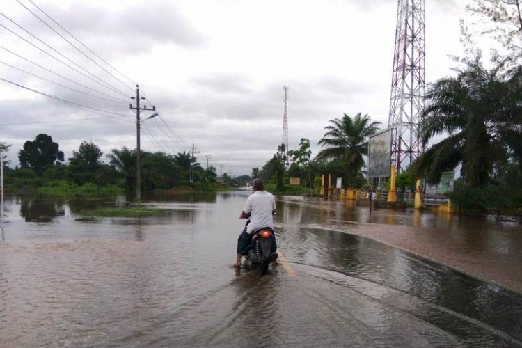 Masyarakat berhenti di jalan nasional yang terendam banjir di Desa Ketapang Indah, Kecamatan Singkil Utara, Kabupaten Aceh Singkil, Sabtu (10/11/2018)