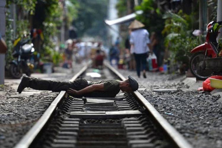Turis berfoto di rel kereta Old Quarter, Vietnam.