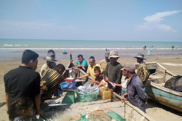Wisatawan memilih ikan untuk dibeli dari nelayan di Pantai Bantayan, Desa Ulee Rubek, Kecamatan Seunuddon, Kabupaten Aceh Utara, Aceh, Minggu (3/2/2019).