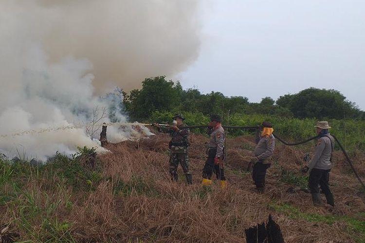 Petugas TNI dan Polri berupaya memadamkan api dengan menggunakan mesin pompa air pada lahan yang terbakar di  Desa Teluk Bano II, Kecamatan Bangko, Rohil, Riau, Rabu (3/7/2019).