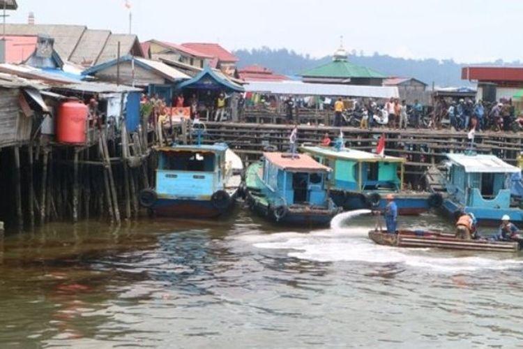 Petugas dari PT Pertamina melakukan penyemprotan untuk membersihkan solar yang mengotori perairan Teluk Balikpapan, Kalimantan Timur, Sabtu (31/3/2018).