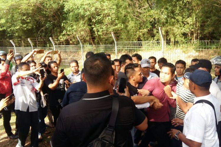 Petugas kepolisian saat mengamankan pengacara Neno Warisman, Mursal Fadillah (baju merah) di gerbang Bandara SSK II Pekanbaru, Riau, Sabtu (25/8/2018).
