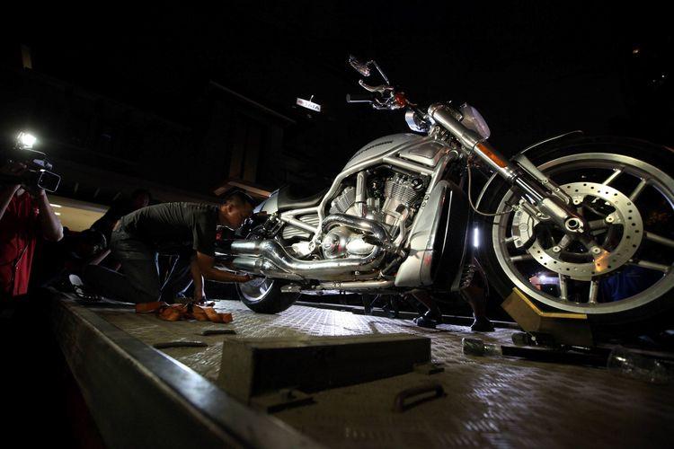 Petugas bersiap membawa sepeda motor Harley Davidson nomor polisi B 3484 NWW dari kediaman tersangka kasus dugaan tindak pidana pencucian uang Tubagus Chaeri Wardana alias Wawan di Jalan Denpasar IV No 35, Kuningan, Jakarta Selatan, Senin (27/1/2014) malam. KPK yang melakukan penggeledahan rumah milik suami Wali Kota Tangerang Selatan Airin Rachmi Diany itu juga menyita mobil Toyota Land Cruiser nomor polisi B 888 TCW, Lexus LS 460 L nomor polisi B 888 ARD, serta mobil sport Nissan GTR nomor polisi B 888 GAW.