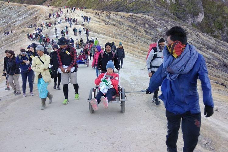 Pengojek atau supir supir taksi mengantarkan wisatawan menuruni jalur pendakian Gunung Ijen, Jawa Timur (9/9/2017). Pengojek atau supir taksi itu akan mengantarkan wisatawan menggunakan gerobak.