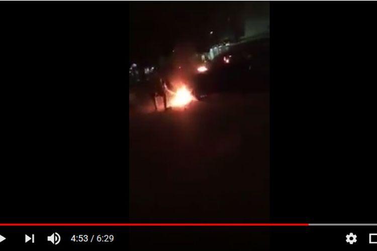 Tampak mobil Suzuki Ignis dibakar massa karena melaju ugal-ugalan dan menabrak pengendara motor dan mobil.