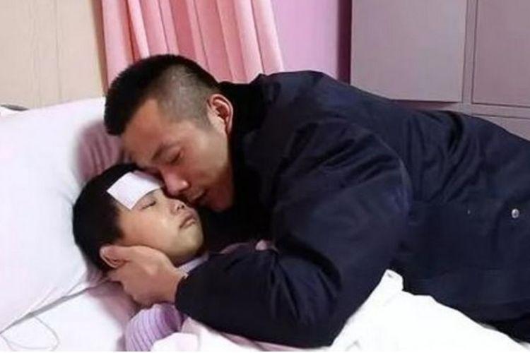 Zhang Jiaye (7), terbaring di ranjang rumah sakit dan dipeluk ayahnya.