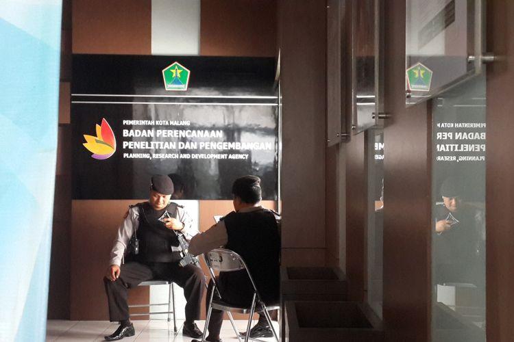 Dua personel polisi saat menjaga Kantor Badan Perencanaan Penelitian dan Pengembangan (Barenlitbang) Kota Malang yang sedang digeledah penyidik KPK, Jumat (11/8/2017)