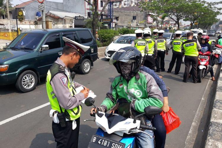 Seorang pengendara sepeda motor ditilang polisi saat terjaring Operasi Zebra di Jalan Margonda Depok, Kamis (1/11/2018).
