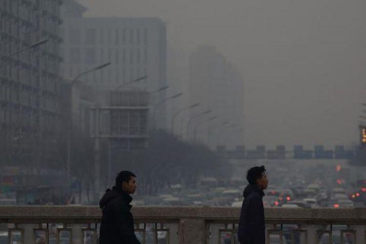 Lalu lintas bergerak sepanjang jalan sebagai pejalan kaki berjalan di sebuah jembatan diselimuti kabut di Beijing, Cina.