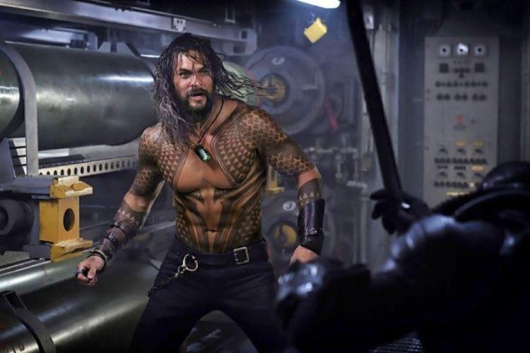 Jason Momoa sebagai Arthur Curry alias Aquaman yang tampak berhadapan dengan sosok misterius dalam baju besi hitam.