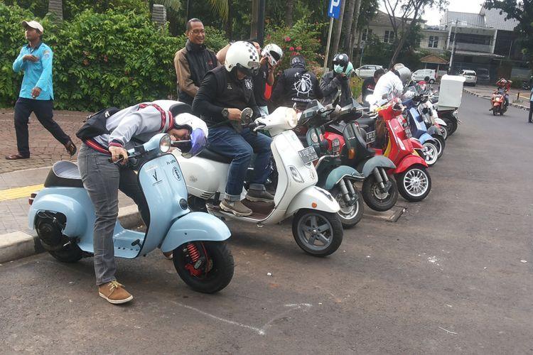 Para anggota komunitas vespa Kutu Community berkumpul di Taman Ayodya, Jakarta Selatan sebelum memulai kegiatan turing santai berkeliling Jakarta pada Senin (1/1/2018).