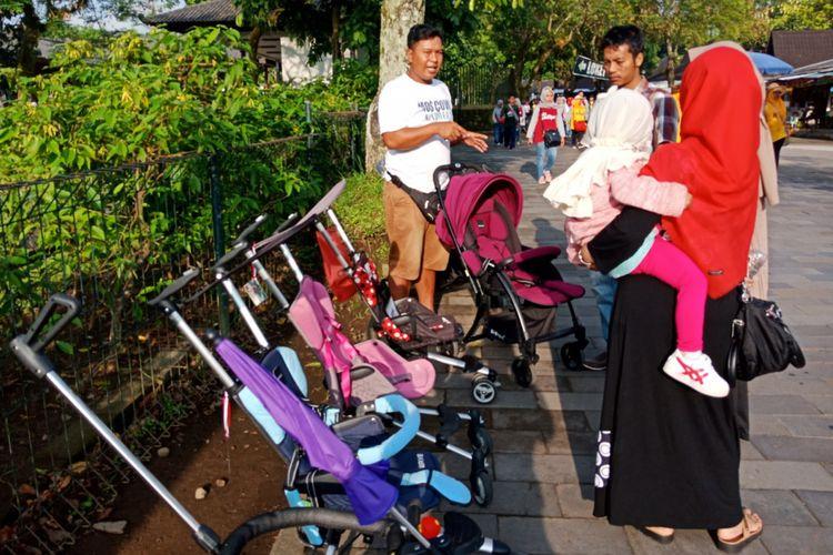 Salah satu keluarga sedang menawar persewaan trolli untuk balita yang tersedia di Candi Borobudur, Magelang, Jawa Tengah ,Sabtu (10/3/2018).
