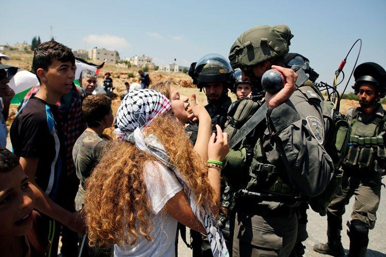 Remaja perempuan Palestina membentak tentara Israel saat aksi demonstrasi di Tepi Barat pada 12 Mei 2017 lalu. Warga Palestina termasuk perempuan dan anak-anak kerap terlihat ikut dalam aksi menentang negara Yahudi tersebut.