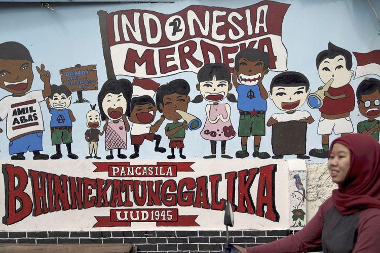 Warga melintas di depan mural Bhinneka Tunggal Ika di Pondok Gede, Bekasi, Jawa Barat, Rabu (27/6/2018). Semboyan bangsa Indonesia, Bhinneka Tunggal Ika, menegaskan, meskipun ada perbedaan di masyarakat, tetapi menjadikan bangsa Indonesia satu kesatuan.   *** Local Caption *** Warga melintas di depan mural Bhinneka Tunggal Ika di Pondok Gede, Bekasi, Rabu (27/6/2018). Semboyan bangsa Indonesia, Bhinneka Tunggal Ika menegaskan bahwa perbedaan di masyarakat menjadikan bangsa Indonesia sebagai suatu kesatuan.