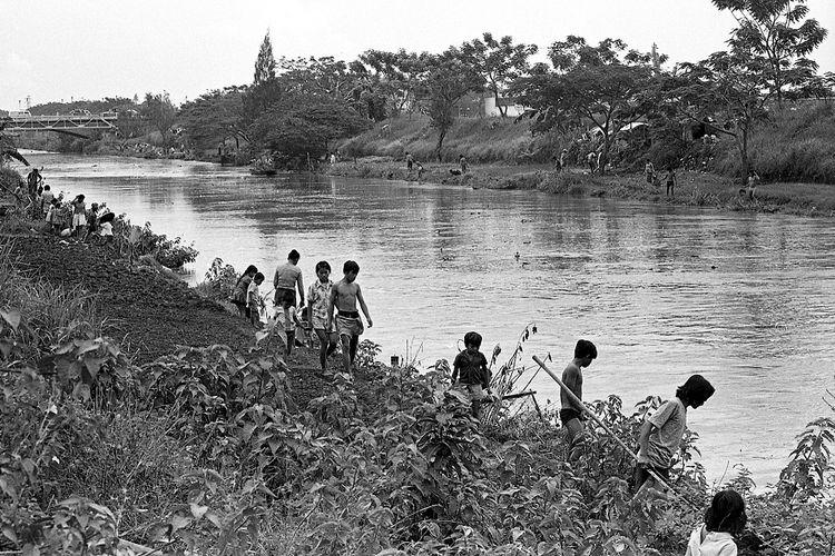 Pada foto yang diambil pada 1 Juli 1974 terlihat warga beramai-ramai menangkap ikan-ikan yang mabuk di Kalimalang.