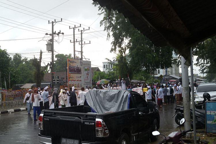 Massa bertahan di depan kantor KPU Kepulauan Bangka Belitung meskipun diguyur hujan, Jumat (26/4/2019).